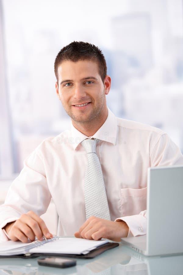 Di impiegato casuale che sorride nell'ufficio fotografia stock libera da diritti