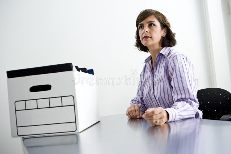 Di impiegato che si siede alla tabella con la casella degli archivi immagini stock