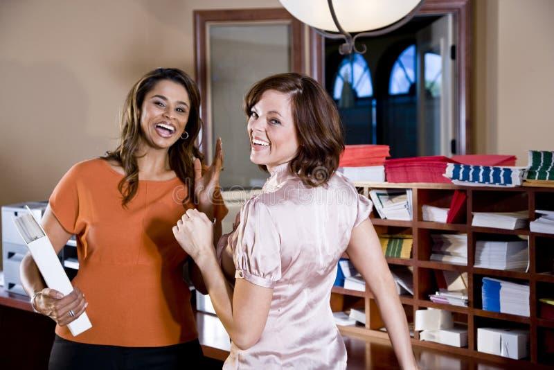 Di impiegato femminili che chiacchierano nella stanza della copia fotografie stock