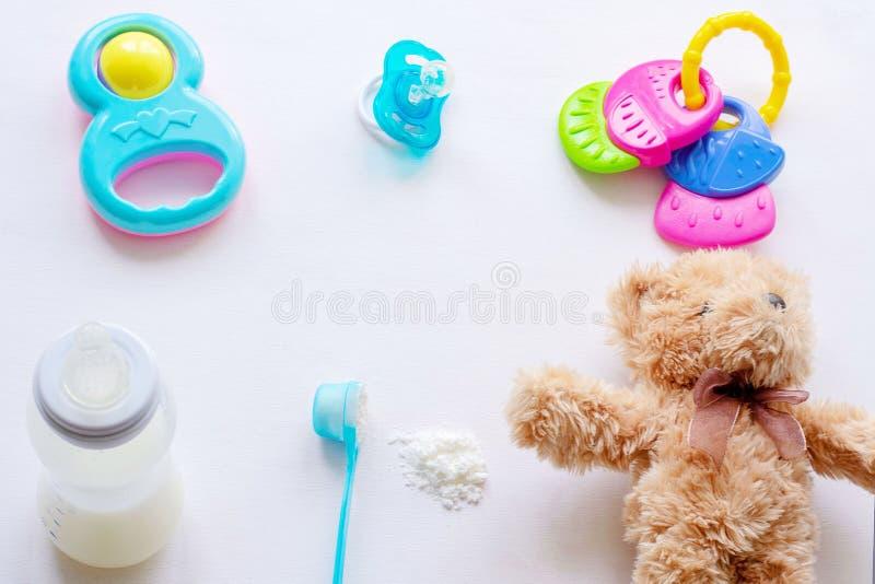 Di latte in polvere del bambino, il biberon ed i giocattoli dei bambini su un fondo leggero piano si situano fotografia stock