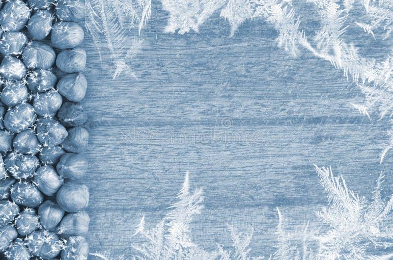 Di legno, tagliere di immagine di inverno con la linea di nocciole Fiocco di neve intorno immagine stock libera da diritti