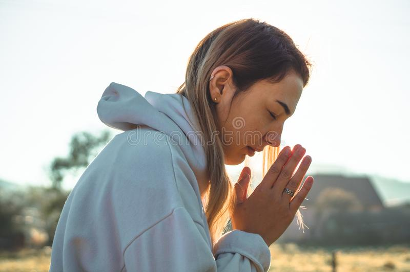 Di mattina la ragazza chiusa lei occhi, pregare all'aperto, mani ha piegato nel concetto di preghiera per fede, la spiritualità,  fotografie stock libere da diritti