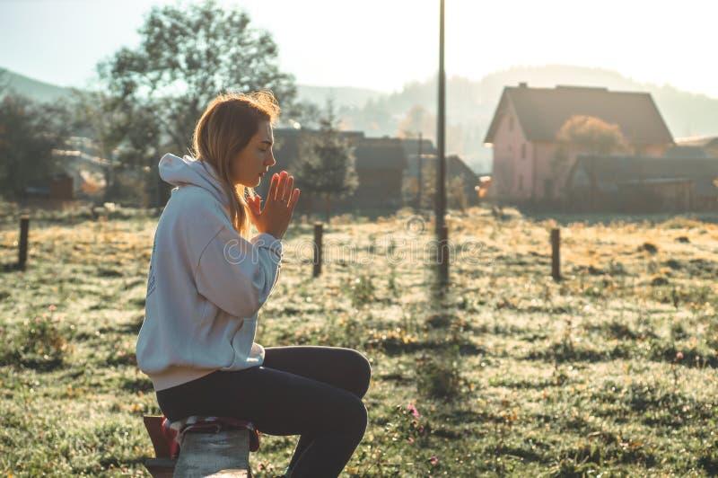 Di mattina la ragazza chiusa lei occhi, pregare all'aperto, mani ha piegato nel concetto di preghiera per fede, la spiritualità,  immagine stock libera da diritti