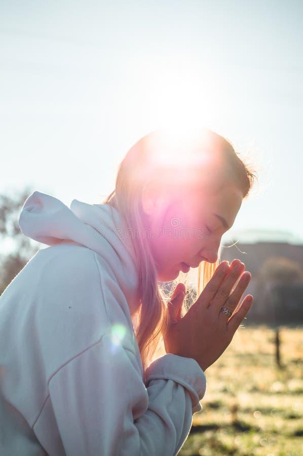Di mattina la ragazza chiusa lei occhi, pregare all'aperto, mani ha piegato nel concetto di preghiera per fede, la spiritualità,  immagini stock
