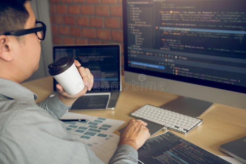 Di mattina di lavoro con uno sviluppatore di programma che tiene un caffè all'ufficio e che esamina lo schermo di computer immagini stock