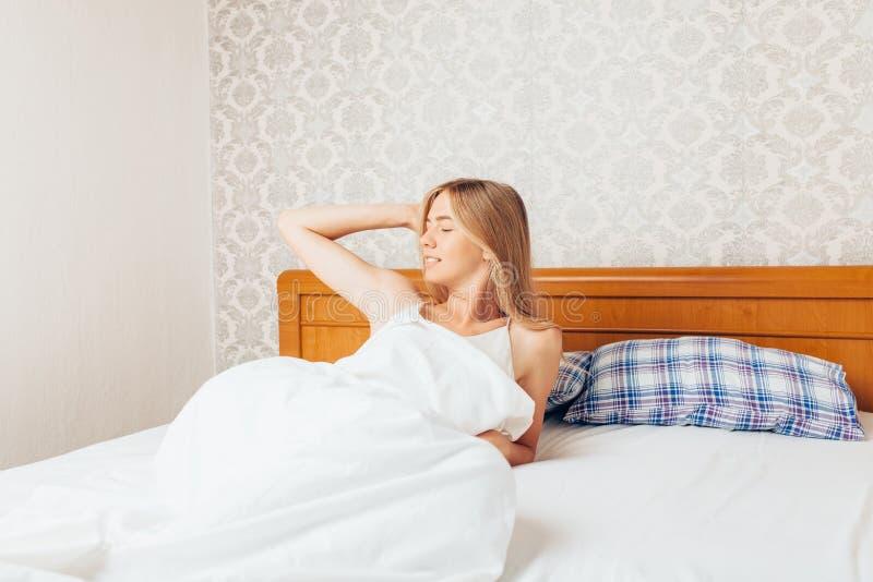 Di mattina una bella ragazza nella camera da letto che ha svegliato e r fotografia stock libera da diritti