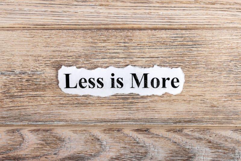 di meno è più testo su carta La parola più di meno è più su carta lacerata Immagine di concetto fotografia stock