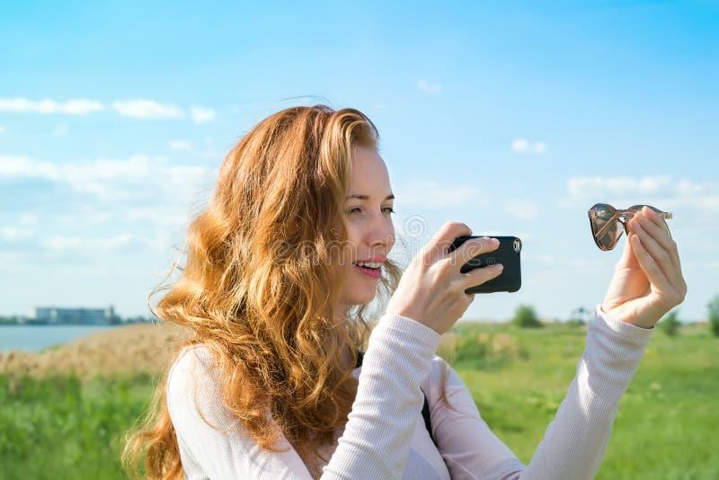 Di modello fotografandosi con lo smartphone immagine stock