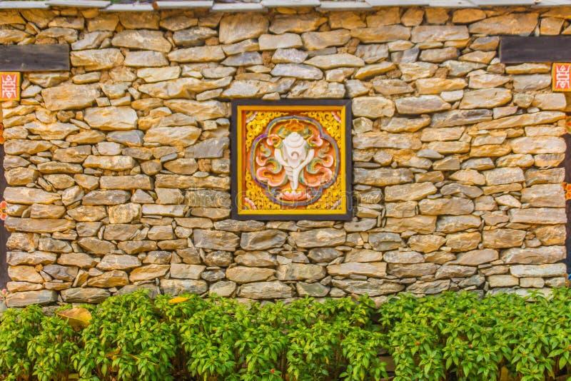 Di muretto di pietra del Bhutanese con materiale illustrativo di legno di scultura variopinto, il cespuglio verde e lo spazio del immagine stock libera da diritti