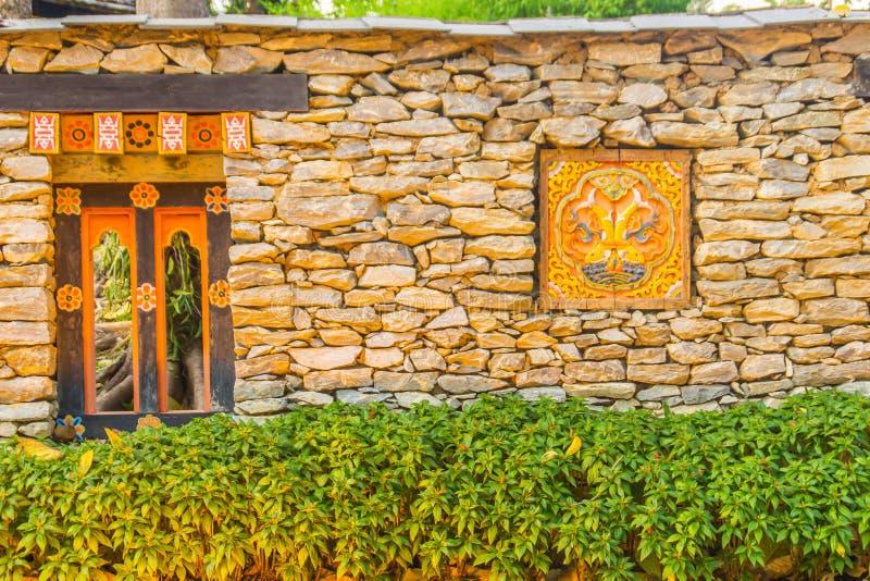Di muretto di pietra del Bhutanese con materiale illustrativo di legno di scultura variopinto, il cespuglio verde e lo spazio del fotografia stock