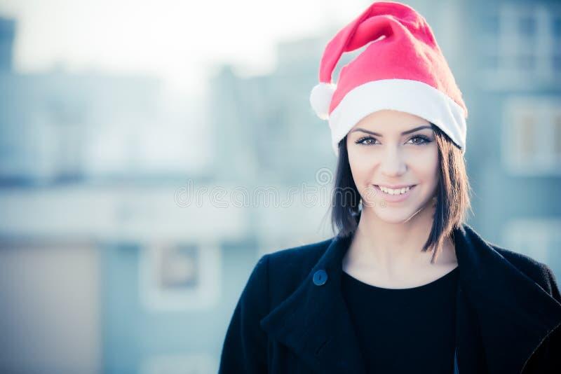 Di Natale di Santa del cappello ritratto sorridente della donna all'aperto Ragazza felice sorridente che porta il suo cappello di fotografia stock libera da diritti