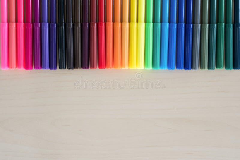 Di nuovo agli accessori variopinti delle penne della cancelleria della scuola su fondo di legno, vista superiore immagine stock libera da diritti