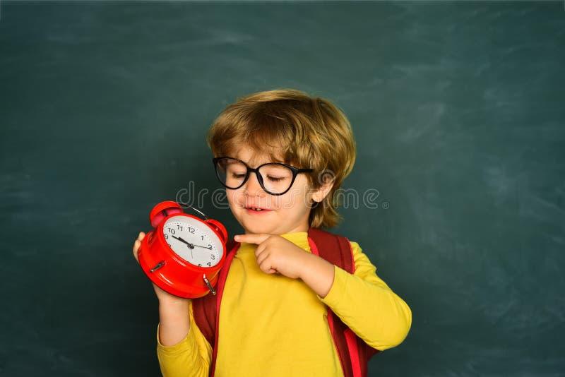 Di nuovo al banco Ansia della sveglia late Allarme dell'orologio della tenuta del ragazzo del bambino immagini stock libere da diritti