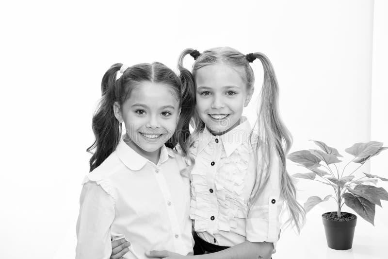 Di nuovo al banco Bambine felici in uniforme Di nuovo al concetto del banco Bambine con capelli alla moda isolati su bianco fotografia stock