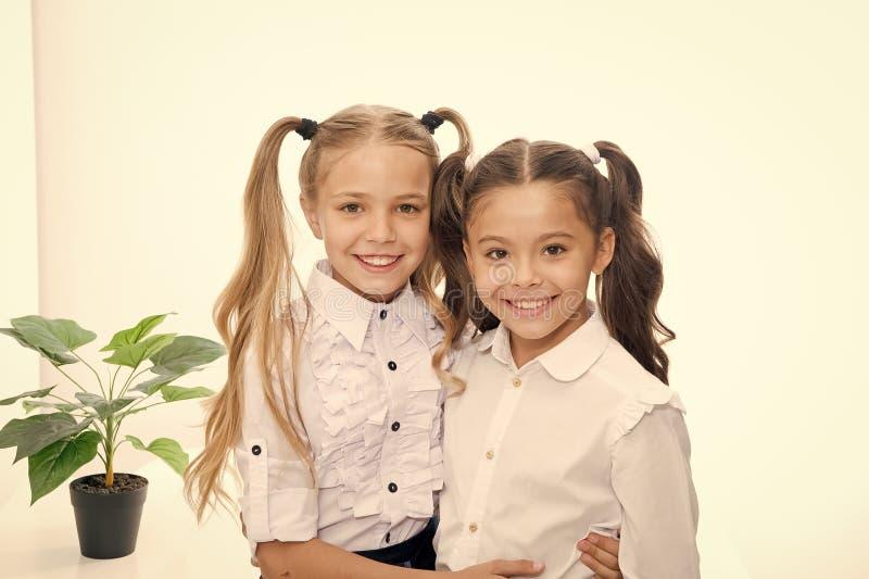 Di nuovo al banco Bambine felici in uniforme Di nuovo al concetto del banco Bambine con capelli alla moda isolati su bianco fotografia stock libera da diritti