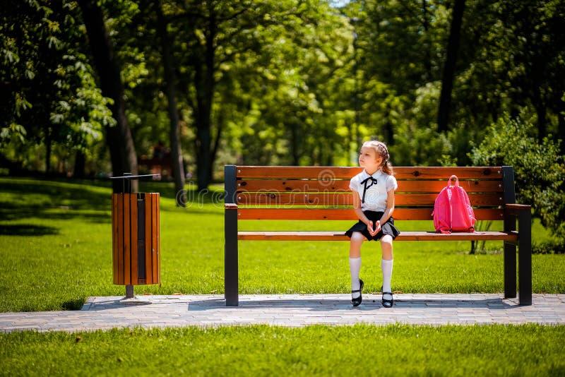 Di nuovo al banco Bambino industrioso sveglio felice che si siede sul banco e che guarda meditatamente al lato Concetto di immagini stock