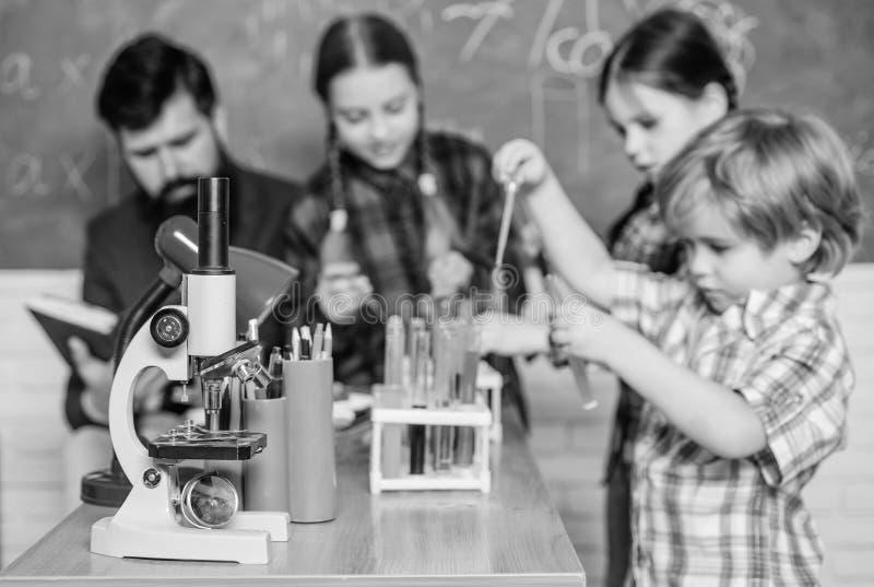 Di nuovo al banco Concetto educativo scienziati dei bambini che fanno gli esperimenti in laboratorio Allievi nella classe di chim immagini stock