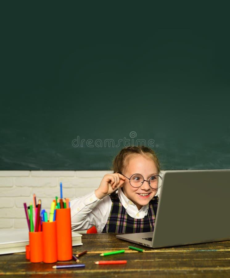 Di nuovo al banco Il bambino sta imparando nella classe su fondo della lavagna Ragazza dell'allievo che lavora ad un computer por fotografia stock libera da diritti