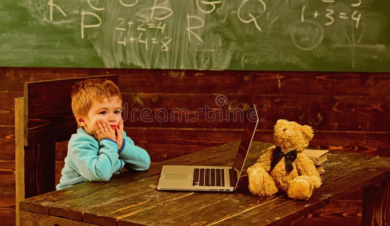 Di nuovo al banco Il ragazzino è di nuovo alla scuola Di nuovo alla scuola con nuova tecnologia Di nuovo alla scuola ed allo sgua fotografia stock