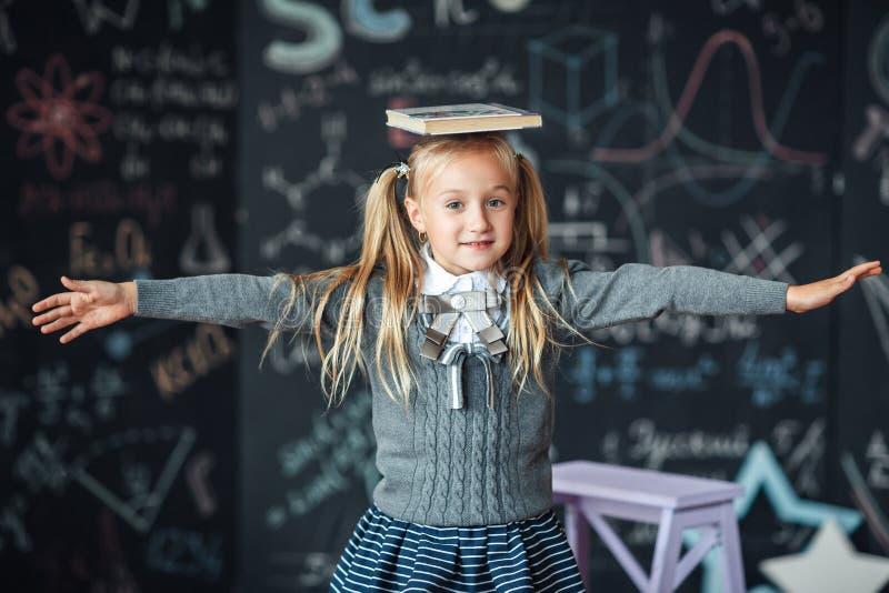 Di nuovo al banco poca ragazza bionda nel bambino dell'uniforme scolastico da scuola elementare tiene i libri sulla sua testa Ist immagini stock libere da diritti