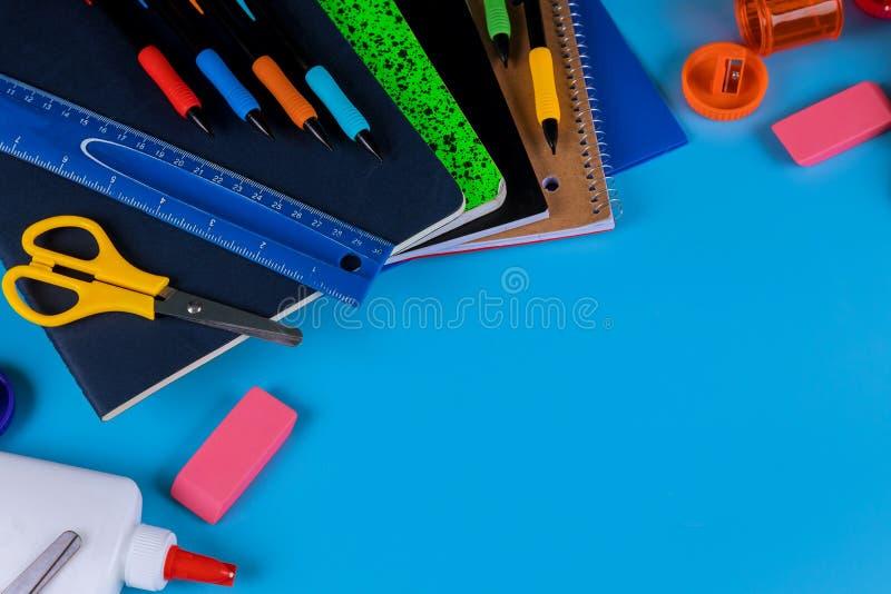 Di nuovo al banco Rifornimenti di scuola su fondo blu immagini stock