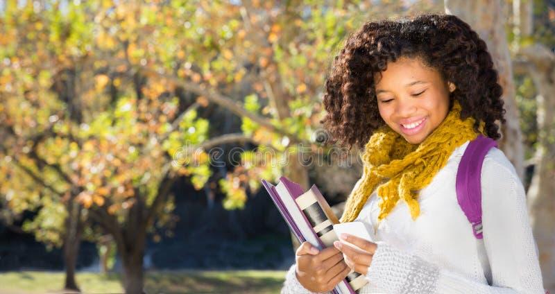 Di nuovo al banco Studentessa abbastanza giovane con il telefono cellulare immagini stock libere da diritti