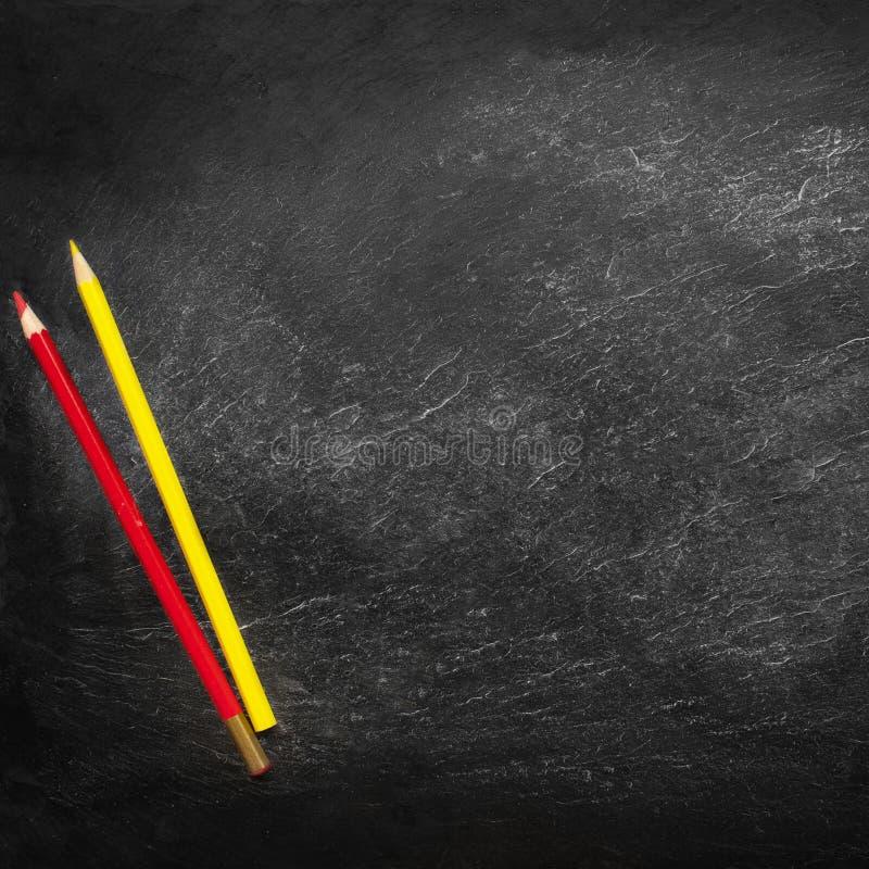 Di nuovo al concetto del banco Fondo di istruzione con copyspace e matite colourful sulla vecchia lavagna vuota nera fotografie stock libere da diritti