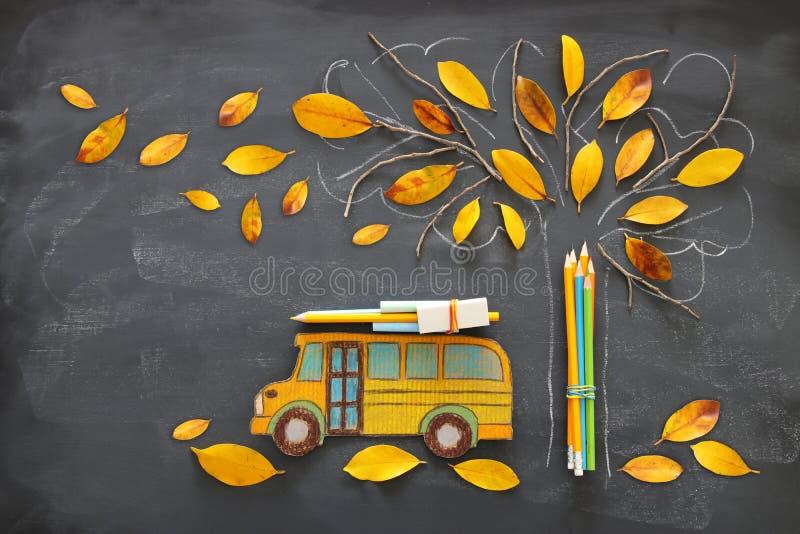 Di nuovo al concetto del banco L'immagine di vista superiore dello scuolabus e delle matite accanto allo schizzo dell'albero con  royalty illustrazione gratis