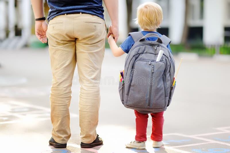 Di nuovo al concetto del banco Piccolo allievo con suo padre Primo giorno della scuola primaria fotografia stock libera da diritti