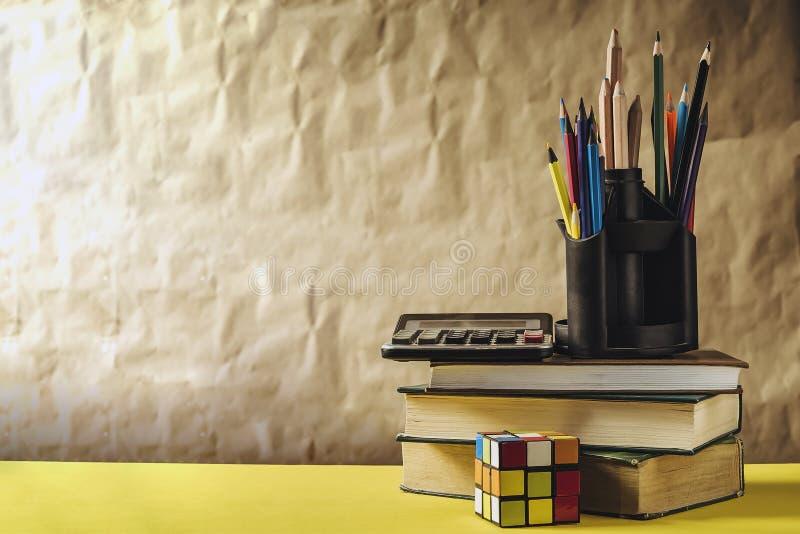 Di nuovo al concetto del banco Pila di libri con i rifornimenti di scuola immagine stock libera da diritti