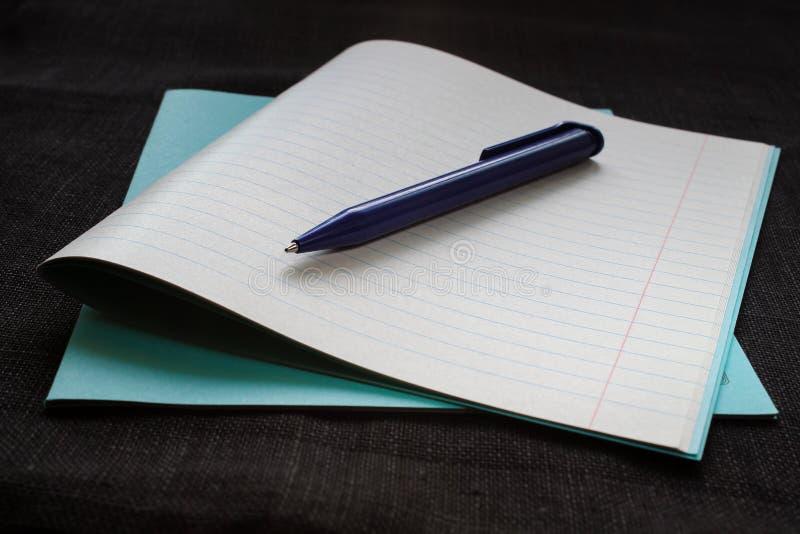 Di nuovo al concetto del banco Taccuino con la carta dell'avviso e penna su fondo nero fotografie stock