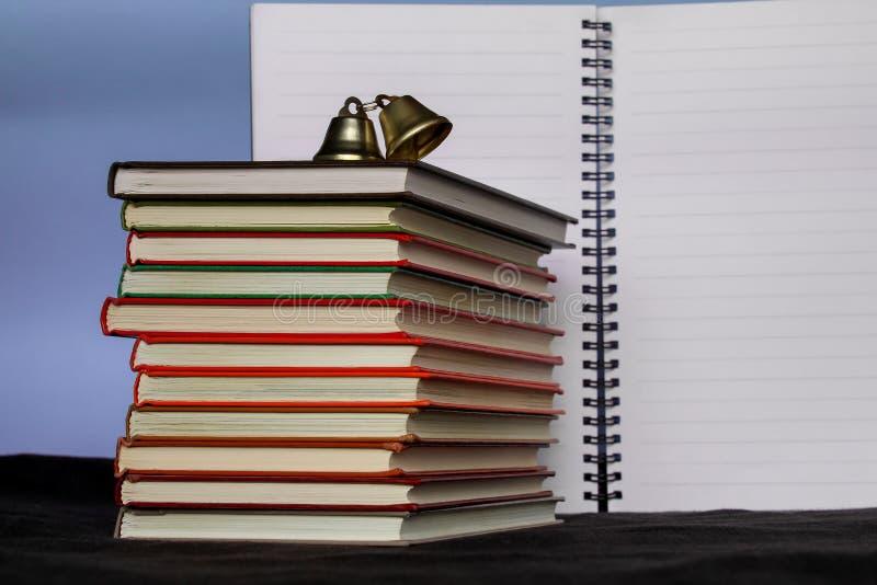 Di nuovo al concetto del banco Un grande mucchio dei libri con un taccuino aperto nei precedenti Copi il testo dello spazio Conce immagine stock libera da diritti