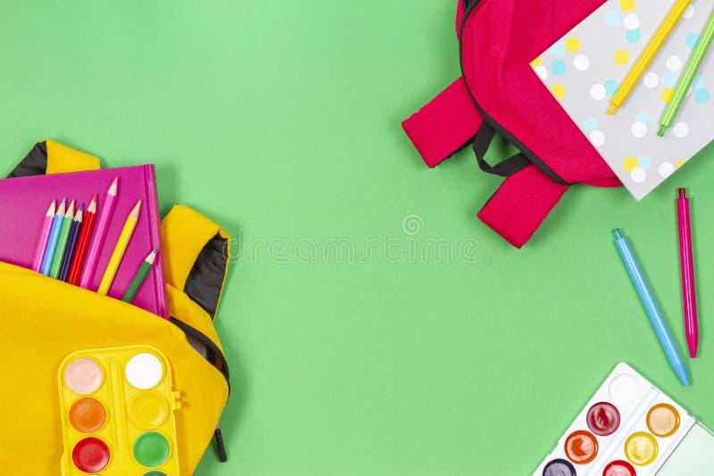 Di nuovo al concetto del banco Zainhi gialli e rosa con i rifornimenti, i libri ed i taccuini di scuola su fondo verde chiaro fotografia stock libera da diritti