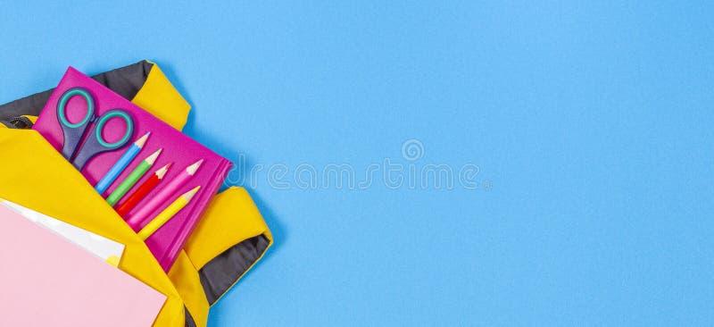 Di nuovo al concetto del banco Zaino giallo con i rifornimenti di scuola su fondo blu-chiaro Vista superiore immagini stock