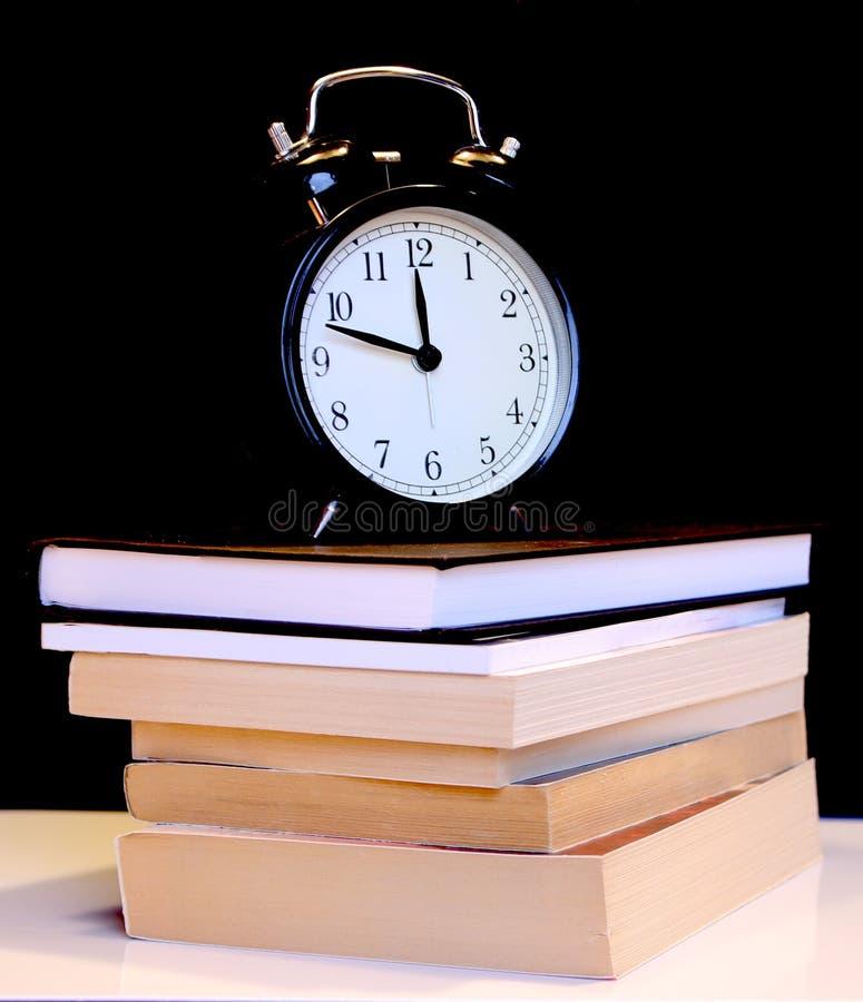 Di nuovo al concetto della scuola con la sveglia, i libri, la mela e le matite Carta per appunti, sveglia, penna e matita immagini stock libere da diritti