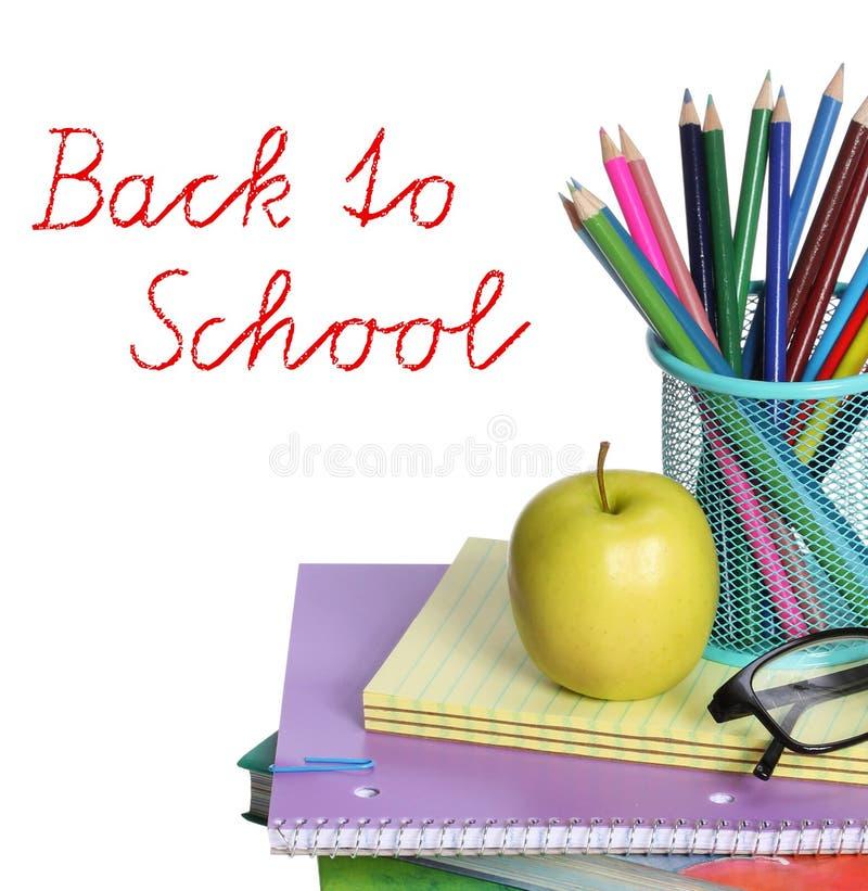 Di nuovo al concetto della scuola. Una mela, le matite colorate ed i vetri sul mucchio dei libri isolati su fondo bianco. immagini stock libere da diritti
