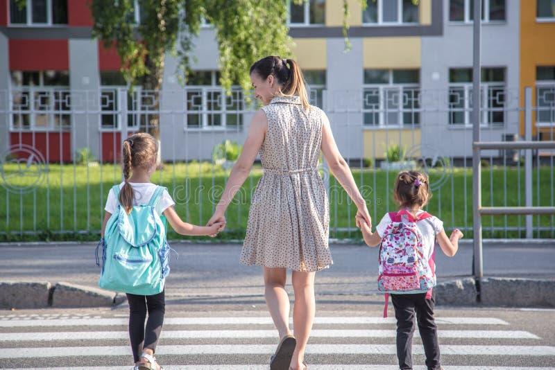 Di nuovo al concetto di istruzione scolastica con i bambini della ragazza, studenti elementari, zainhi di trasporto che vanno cla fotografie stock