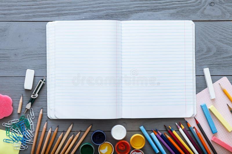Di nuovo al concetto di vendita della scuola, quaderno vuoto aperto sullo scrittorio scuro grigio con le matite variopinte, pittu immagine stock