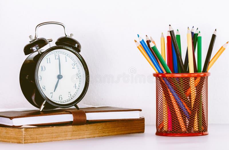 Di nuovo al fondo della scuola con i libri e la sveglia fotografie stock
