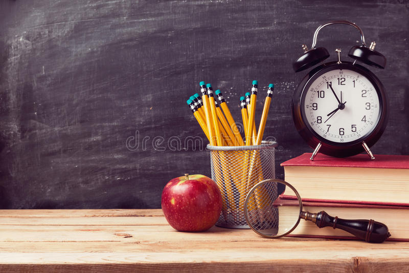 Di nuovo al fondo della scuola con i libri e la sveglia sopra la lavagna immagini stock