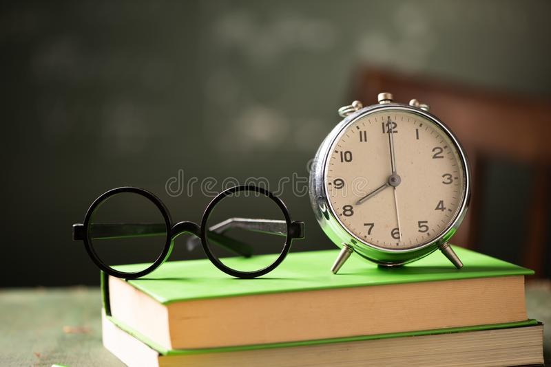 Di nuovo al fondo della scuola con i libri e la sveglia fotografia stock