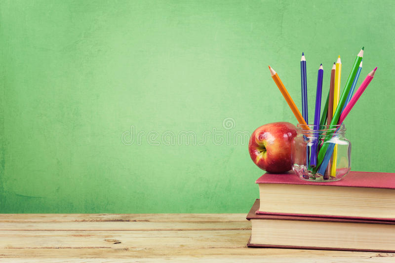 Di nuovo al fondo della scuola con i libri, le matite e la mela di colore fotografie stock libere da diritti