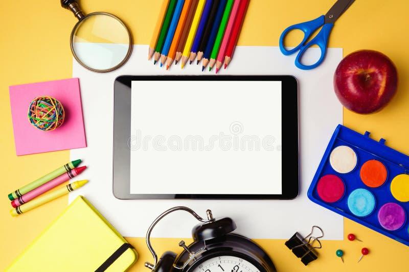 Di nuovo al fondo della scuola con i rifornimenti digitali di scuola e della compressa Vista da sopra immagini stock libere da diritti