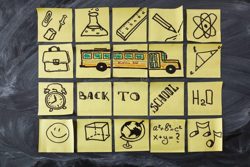 Di nuovo al fondo della scuola con il titolo di nuovo alla scuola, lo scuolabus e la scuola attribuisce scritto su pezzi di carta fotografia stock libera da diritti