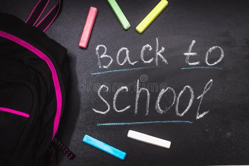 Di nuovo al messaggio della scuola sulla lavagna iscritta con gesso variopinto per fondo fagotto fotografie stock