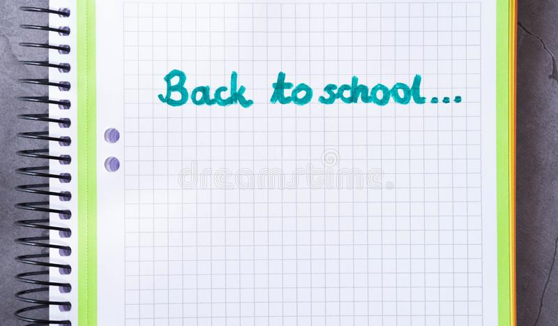 Di nuovo al testo di scuola scritto sul taccuino verde con fondo di pietra immagine stock libera da diritti