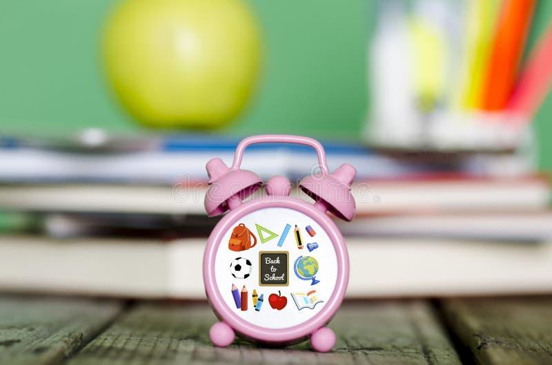 Di nuovo all'illustrazione della scuola sul piccolo orologio con il mucchio dei libri, g fotografie stock