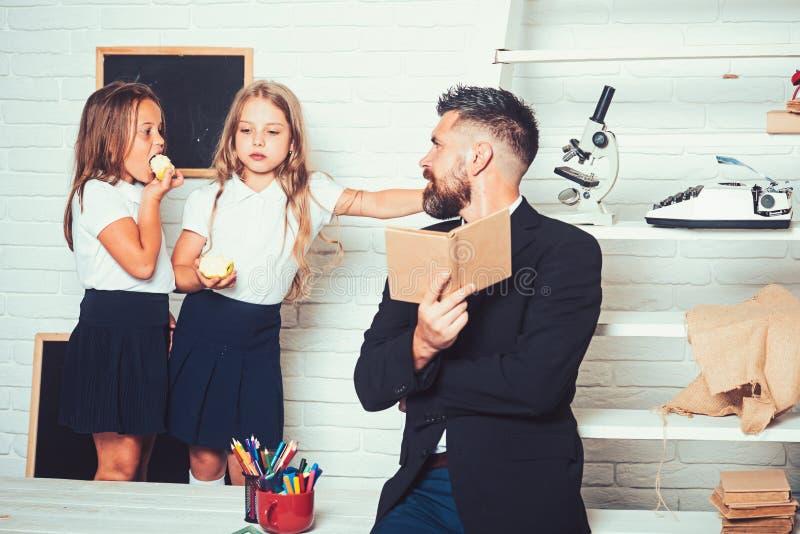 Di nuovo all'istruzione domestica e dello scuola L'uomo dell'insegnante ha letto la storia alle ragazze che mangiano la mela Lezi fotografia stock