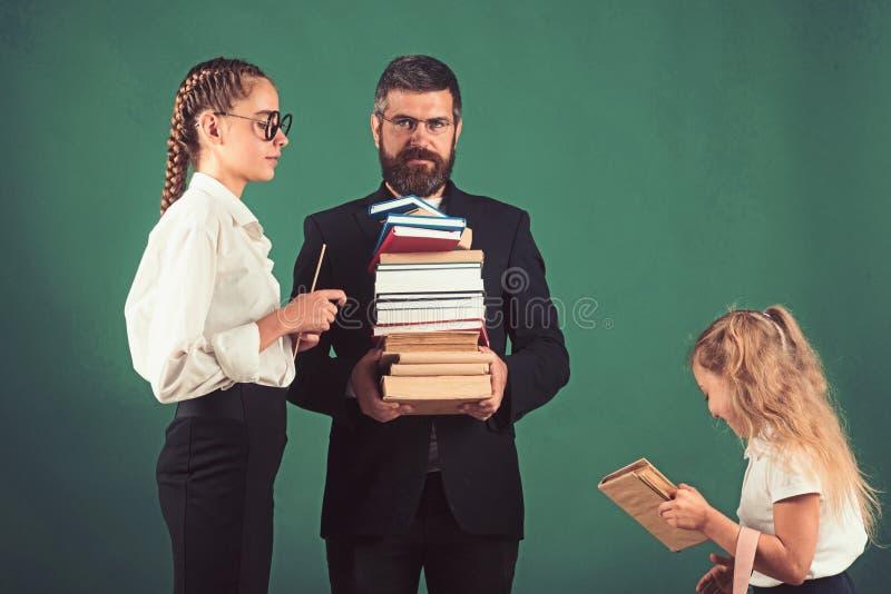 Di nuovo all'istruzione domestica e dello scuola L'uomo e le ragazze dell'insegnante tengono il mucchio del libro a scuola Lezion fotografia stock