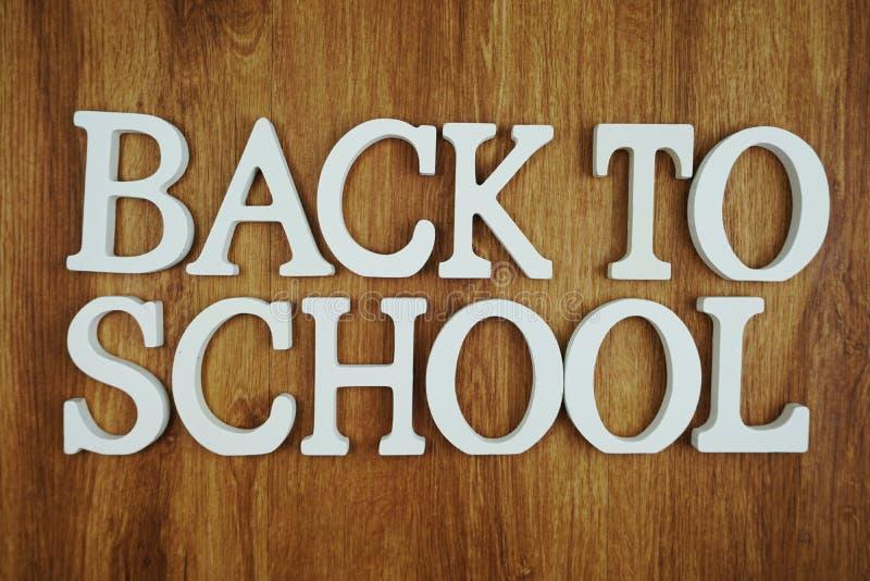 Di nuovo alla lettera di alfabeto della scuola con la copia dello spazio su fondo di legno immagini stock